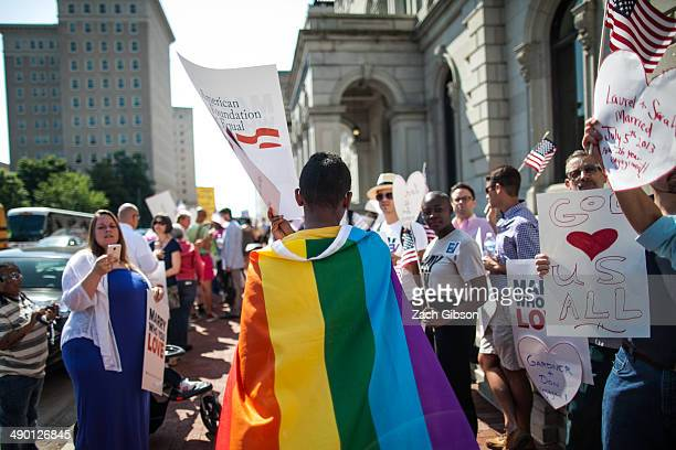 A samesex marriage supporter wears a rainbow cape behind 4th US Circuit Court of Appeals after a court hearing May 13 2014 in Richmond Virginia Three...