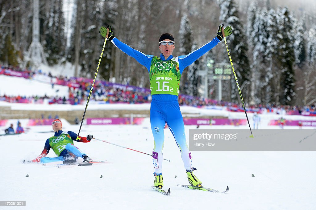 Sami Jauhojaervi of Finland celebrates as he crosses the line to win the gold medal with team mate Iivo Niskanen of Finland (not pictured) as <a gi-track='captionPersonalityLinkClicked' href=/galleries/search?phrase=Nikita+Kriukov&family=editorial&specificpeople=4907513 ng-click='$event.stopPropagation()'>Nikita Kriukov</a> of Russia collapses in the snow in the Men's Team Sprint Classic Final during day 12 of the 2014 Sochi Winter Olympics at Laura Cross-country Ski & Biathlon Center on February 19, 2014 in Sochi, Russia.