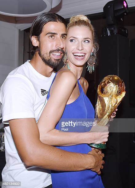 Sami Khedira of Germany and girlfriend Lena Gercke pose with the World Cup trophy as he celebrates with teammates at a party after winning the 2014...