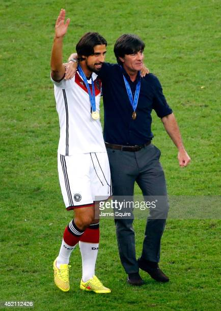 Sami Khedira of Germany celebrates with head coach Joachim Loew after defeating Argentina 10 in extra time during the 2014 FIFA World Cup Brazil...