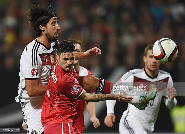 Sami Khedira of Germany challenges for the ball with Ryan Casciaro of Gibraltar during the EURO 2016 Group D Qualifier match between Germany and...