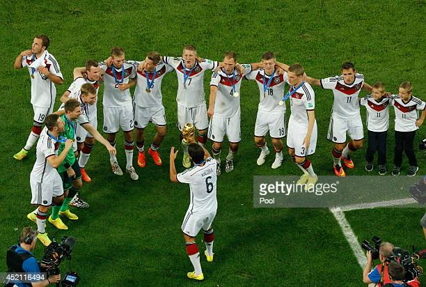 Sami Khedira of Germany hold the World Cup trophy and celebrates with teammates after defeating Argentina 10 in extra time during the 2014 FIFA World...