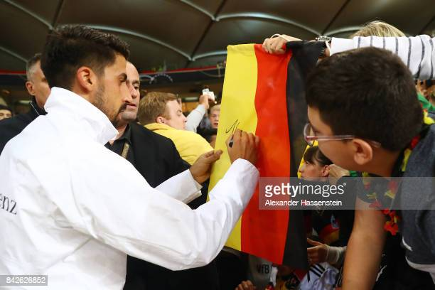 Sami Khedira of Germany signed a German flag of fans after the FIFA 2018 World Cup Qualifier between Germany and Norway at MercedesBenz Arena on...
