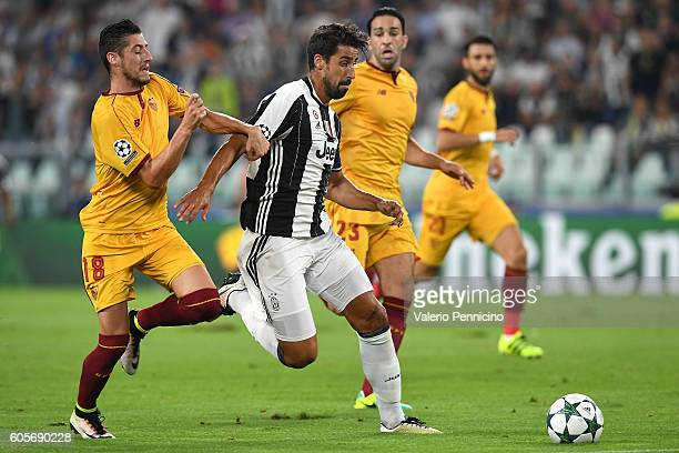 Sami Khedira of Juventus FC is challenged by Sergio Escudero of Sevilla FC during the UEFA Champions League Group H match between Juventus FC and...