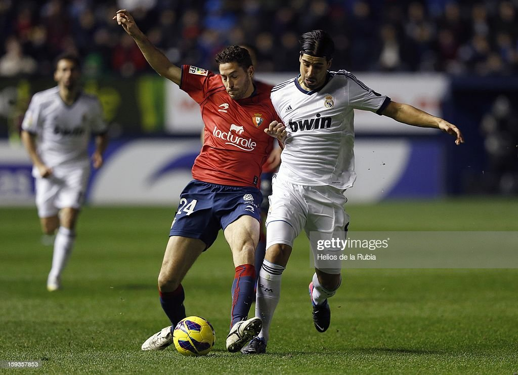 Sami Khedira of Real Madrid CF duels for the ball with Damia Abella of CA Osasuna during the La Liga match between CA Osasuna and Real Madrid CF at Estadio Reyno de Navarra on January 12, 2013 in Pamplona, Spain.