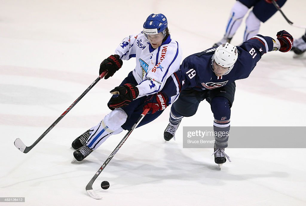Sami Niku #4 of Team Finland move sthe puck around Sean Malone #19 of USA Blue during the 2014 USA Hockey Junior Evaluation Camp at the Lake Placid Olympic Center on August 3, 2014 in Lake Placid, New York. USA Blue defeated Team Finland 2-1.