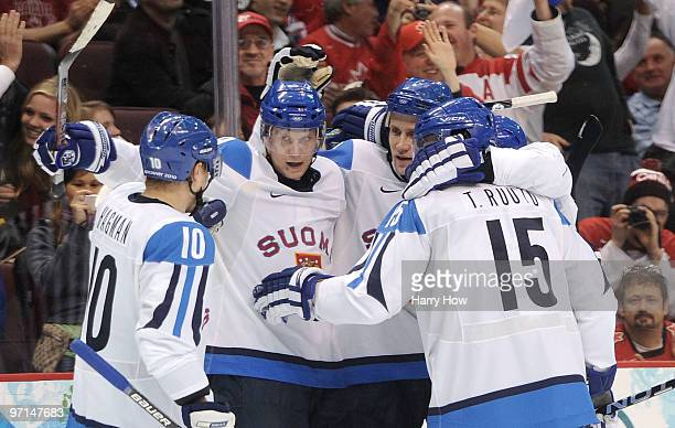 Sami Salo of Finland celebrates with Mikko Koivu and his team after scoring a goal in the first period during the ice hockey men's bronze medal game...