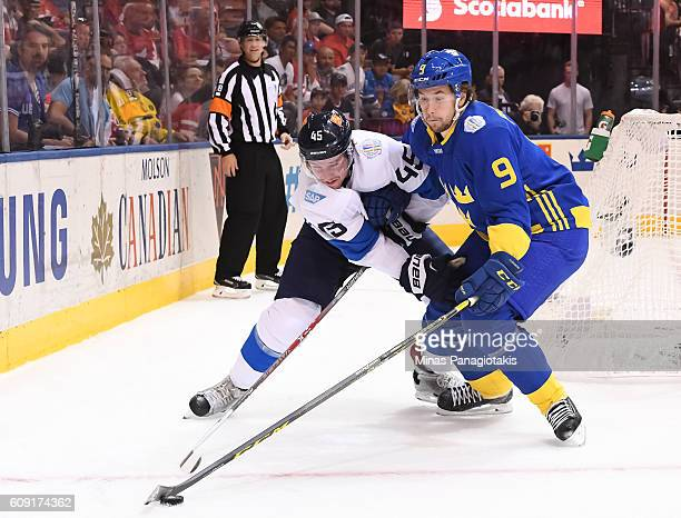 Sami Vatanen of Team Finland battles for a loose puck with Filip Forsberg of Team Sweden during the World Cup of Hockey 2016 at Air Canada Centre on...