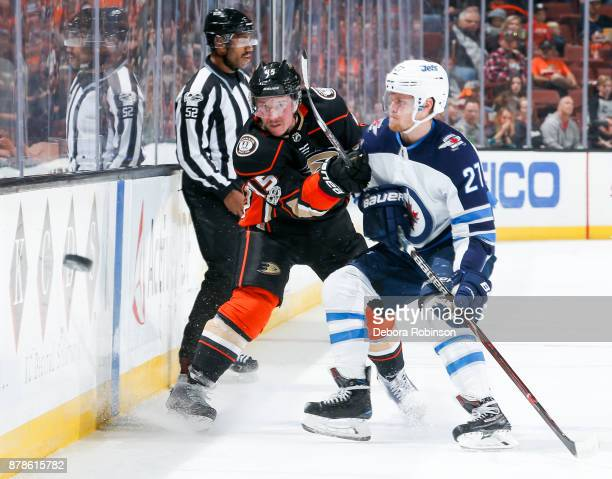 Sami Vatanen of the Anaheim Ducks sends the puck downice with pressure from Nikolaj Ehlers of the Winnipeg Jets during the first period of the game...