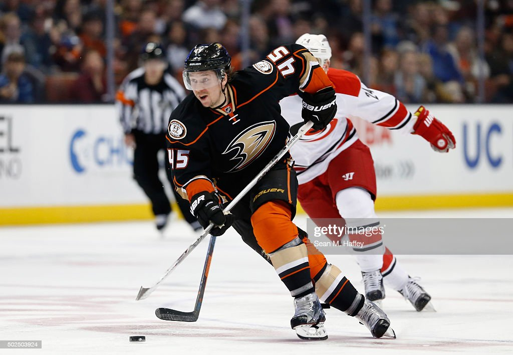 Sami Vatanen of the Anaheim Ducks skates past Brad Malone of the Carolina Hurricanes during a game at Honda Center on December 11 2015 in Anaheim...