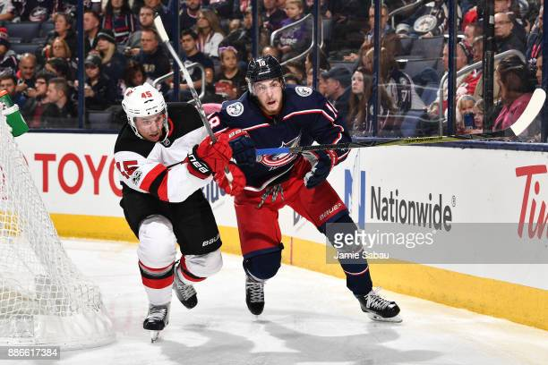 Sami Vatanen of the New Jersey Devils and PierreLuc Dubois of the Columbus Blue Jackets battle for position as they skate after a loose puck during...