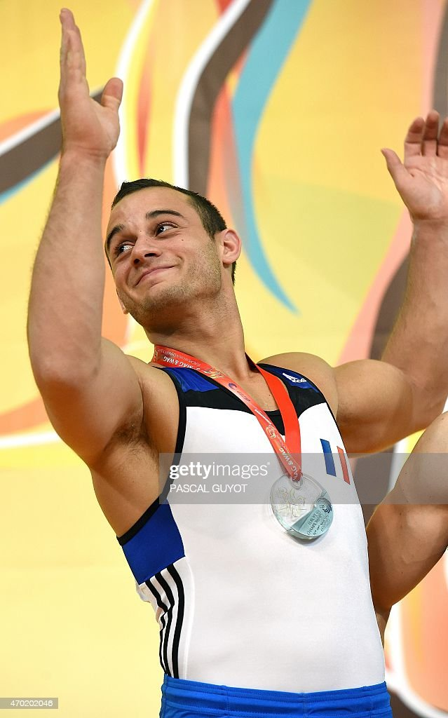 Samir Ait Said of France applauds on the podium after winning a silver medal during the medal ceremony for the Rings event during the European Men's artistic gymnastics individual championships in Montpellier, southern France on April 18, 2015.