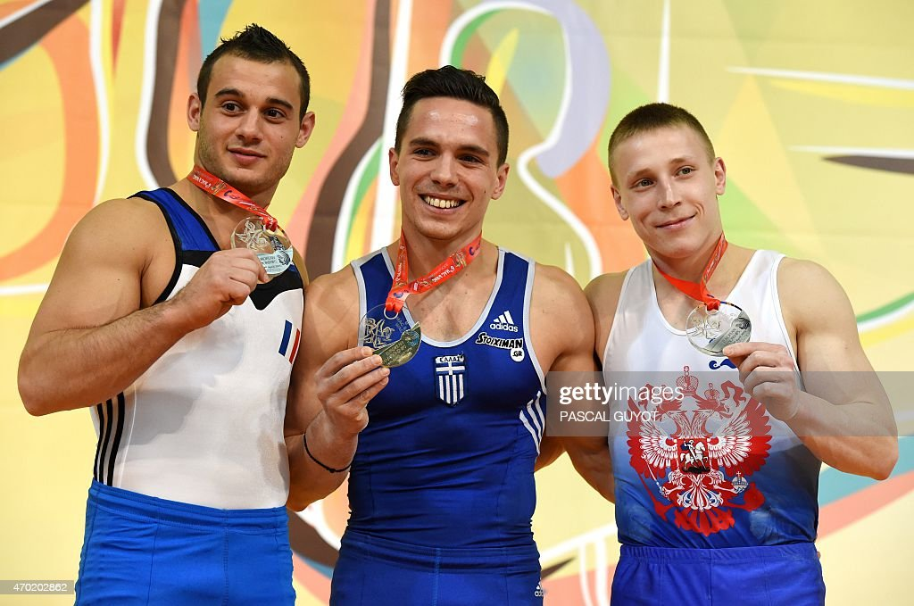 Samir Ait Said (L) of France, Eleftherios Petrounias (C) of Greece and Denis Abliazin (R) of Russia pose on the podium during the medal ceremony for the Rings event during the European Men's artistic gymnastics individual championships in Montpellier, southern France on April 18, 2015. Petrounias took the gold medal, while Ait Said and Abliazin took joint silver. AFP PHOTO / PASCAL GUYOT