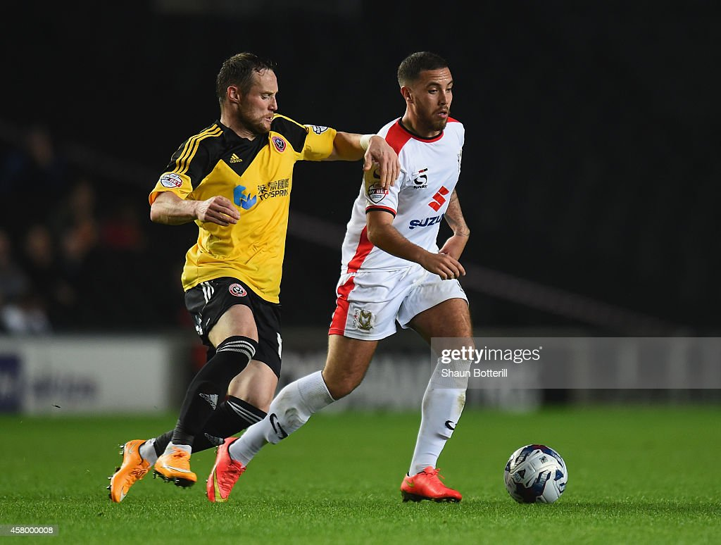 Samir Carruthers of MK Dons is challenged by Ben Davies of Sheffield United during the Capital One Cup Fourth Round match between MK Dons and Sheffield United at Stadium mk on October 28, 2014 in Milton Keynes, England.