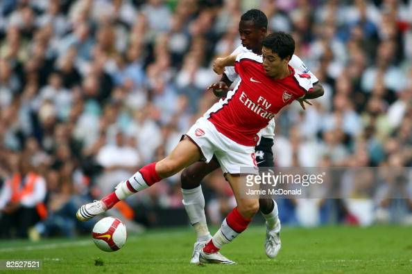Samir Nasri of Arsenal battles for the ball with John Pantsil of Fulham during the Barclays Premier League match between Fulham and Arsenal at Craven...