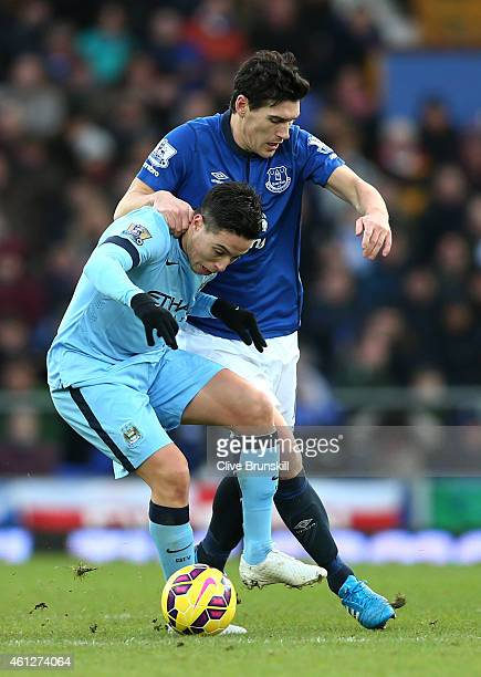 Samir Nasri of Manchester City and Gareth Barry of Everton battle for the ball during the Barclays Premier League match between Everton and...