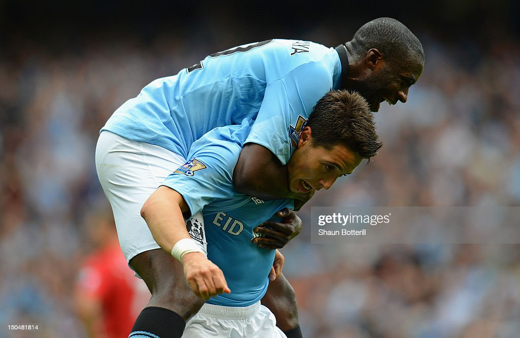 Samir Nasri of Manchester City celebrates scoring his team's third goal with team mate Yaya Toure (top) during the Barclays Premier League match between Manchester City and Southampton at Etihad Stadium on August 19, 2012 in Manchester, England.