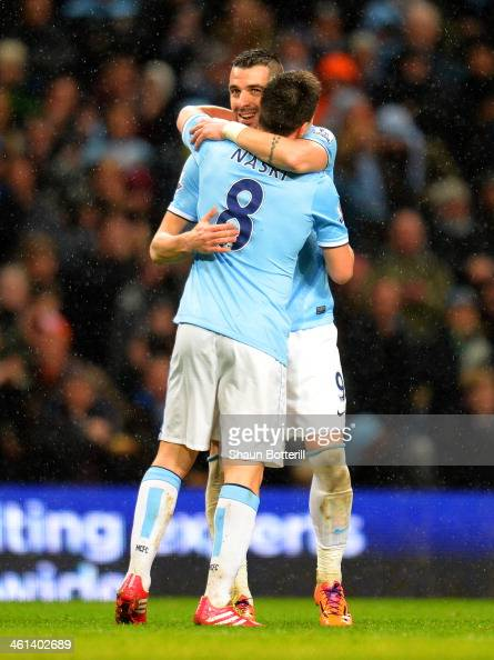 Samir Nasri of Manchester City congratulates Alvaro Negredo of Manchester City on scoring their fourth goal and his hat trick during the Capital One...