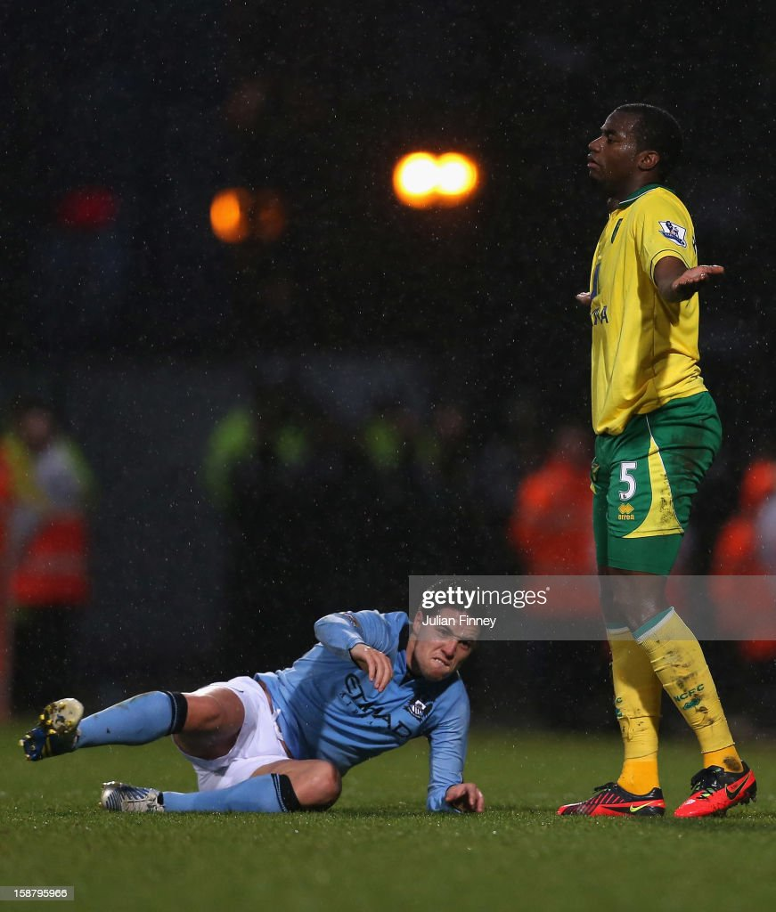 Samir Nasri of Manchester City reacts after he is tackled by Sebastien Bassong of Norwich City during the Barclays Premier League match between...