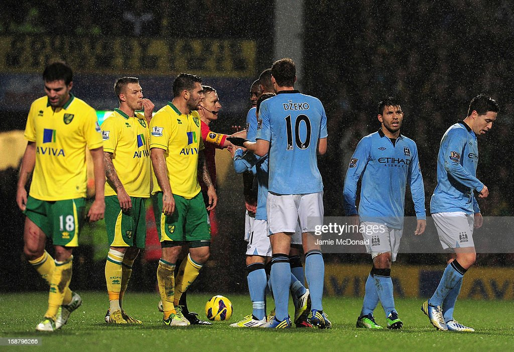 Samir Nasri of Manchester City (R) walks off the pitch after he is shown the red card by referee Mike Jones after he head butts Sebastien Bassong of Norwich City during the Barclays Premier League match between Norwich City and Manchester City at Carrow Road on December 29, 2012 in Norwich, England.