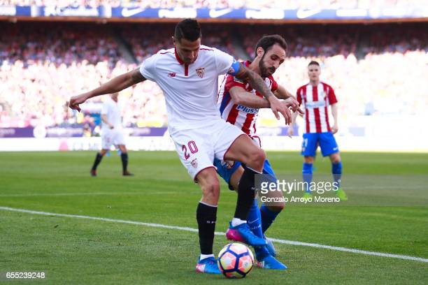 Samir Nasri of Sevilla FC competes for the ball with Juan Francisco Torres alias Juanfran of Atletico de Madrid during the La Liga match between Club...