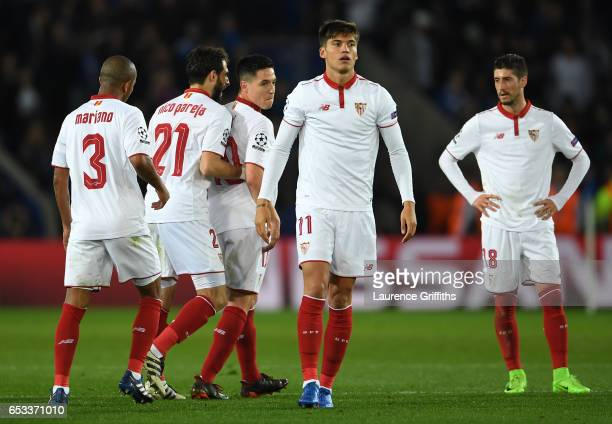 Samir Nasri of Sevilla is shepherded off the pitch by teammates after he was shown the red card during the UEFA Champions League Round of 16 second...
