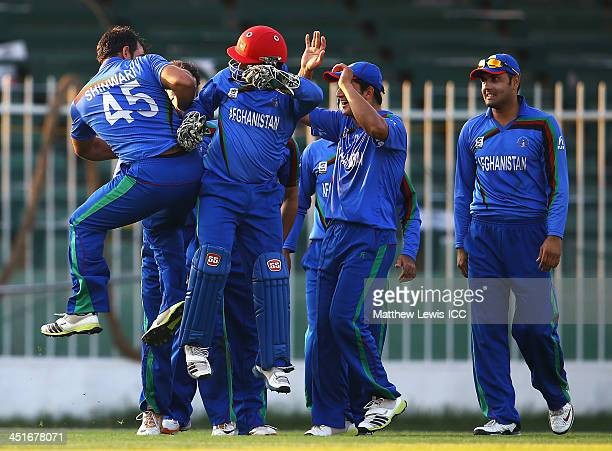 Samiullah Shenwari and Mohammad Shahzad of Afghanistan celebrate the wicket of Collins Obuya of Kenya after he was stumped during the ICC World...