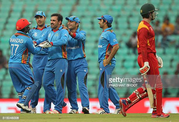 Samiullah Shinwari of Afganistan celebrates the wicket of Malcom Waller of Zimbabwe with teammates during the T20 World Cup cricket match between...