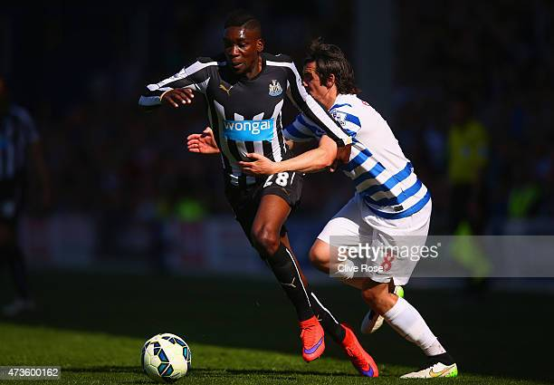 Sammy Ameobi of Newcastle United is challenged by Joey Barton of QPR during the Barclays Premier League match between Queens Park Rangers and...