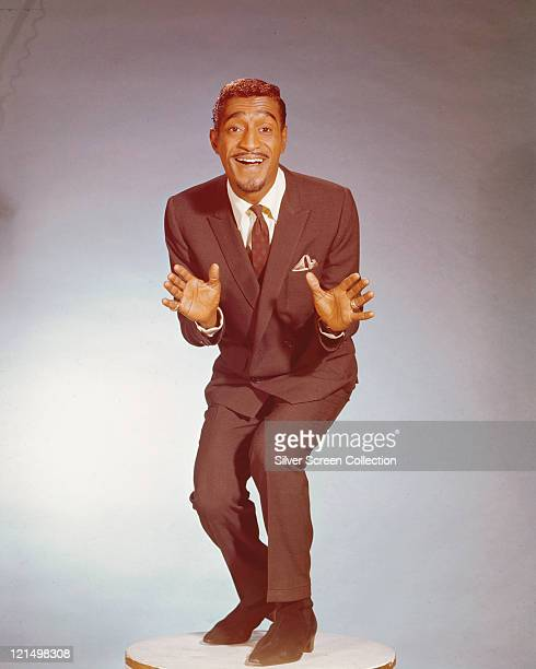 Sammy Davis Jr US singer actor and dancer holding a dance pose in a studio portrait against a grey background circa 1960