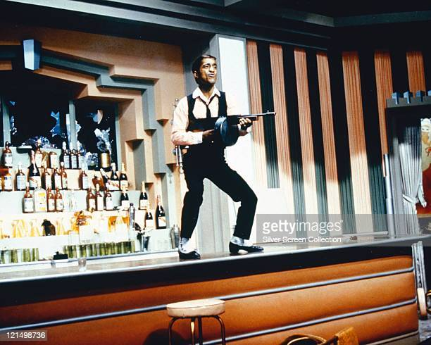 Sammy Davis Jr US singer actor and dancer standing on a bar holding a tommy gun in a publicity still issued for the film 'Robin and the 7 Hoods' 1964...