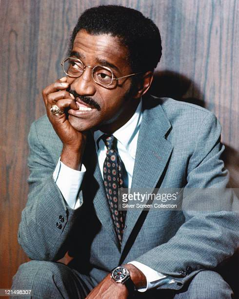 Sammy Davis Jr US singer actor and dancer wearing a grey suit white shirt and patterned blue tie with his chin resting on his hand circa 1970