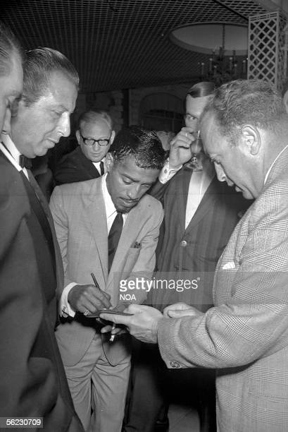 Sammy Davis Junior American singer and actor signing some autographs Festival of Cannes 1966 HA10502