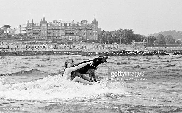 Sammy the water skiing dog with his mistress with the Grand Hotel in the background in Torquay South Devon circa 1970