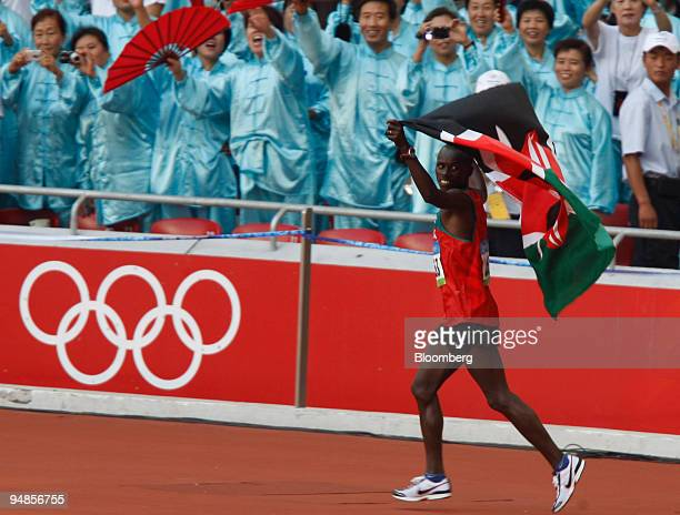 Sammy Wanjiru of Kenya runs with his national flag in the National Stadium also called the Bird's Nest after winning the men's marathon on day 16 of...
