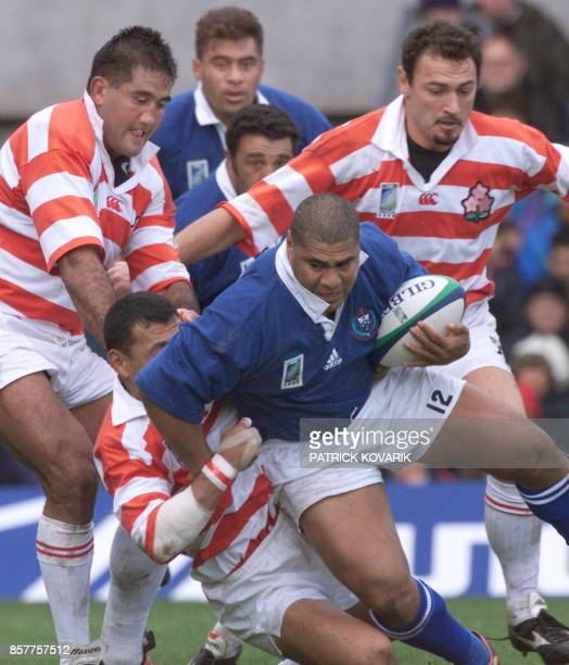 Samoan centre Va'aiga Tuigamala tries to break away from the tackle of Japanese Jamie Joseph and Greg Smith during the Rugby World Cup firstround...