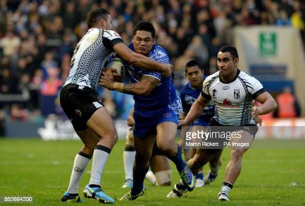 Samoa's Joseph Leilua is tackled by Fiji's Daryl Millard during the World Cup Quarter Final at the Halliwell Jones Stadium Warrington