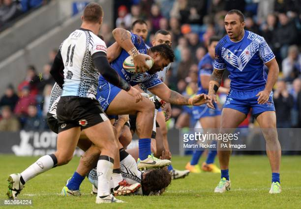 Samoa's Mose Masoe is tackled by Fiji's Kane Evans and Fiji's Ashton Sims during the World Cup Quarter Final at the Halliwell Jones Stadium Warrington