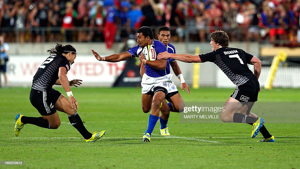 Samoa's Reupena Levasa (C) is tackled by New Zealand's Ben Lam and Sam Dickson (R) with Samoa's Levi Asifa'amatala (rear) in support during 3rd/4th playoff at the Westpac Stadium on day two of the fourth leg of the IRB Rugby Sevens World Series in Wellington on February 2, 2013. AFP PHOTO / Marty MELVILLE
