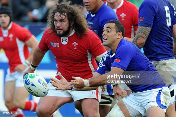 Samoa's scrumhalf Kahn Fotuali'i passes the ball in front of Wales' prop Adam Jones during the 2011 Rugby World Cup pool D match Wales vs Samoa at...