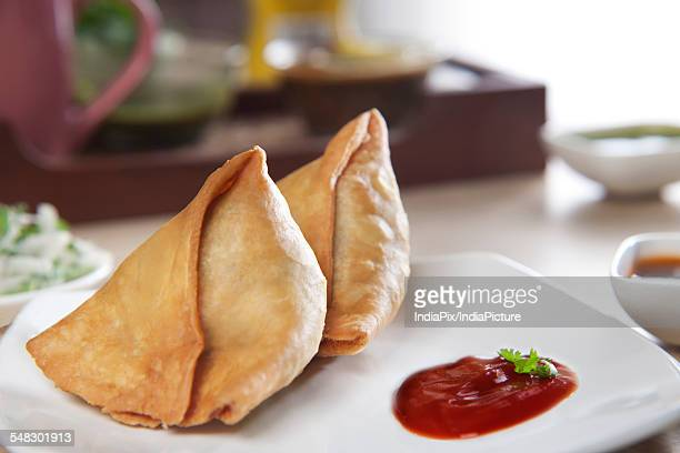 Samosas with tomato ketchup in plate