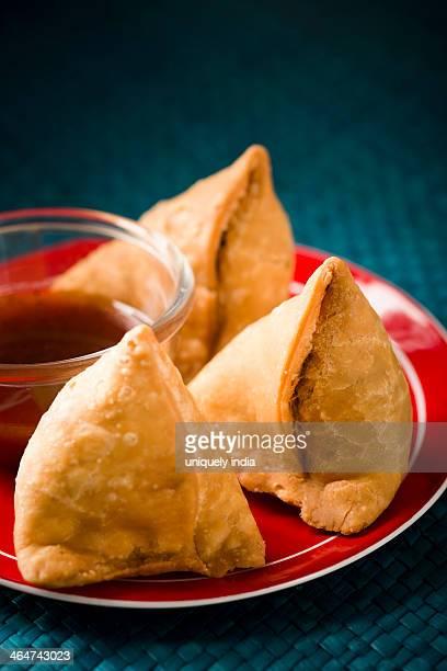 Samose served with chutney on a plate