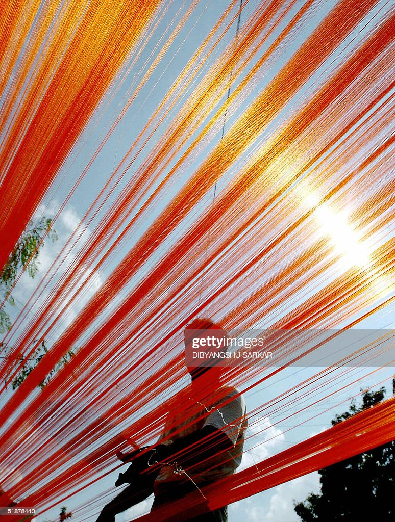 STORY 'WTOTEXTILESTRADEINDIA' Sampath Kumar a 29yearold Indian weaver is pictured through silk threads drying under the sun which will be used to...