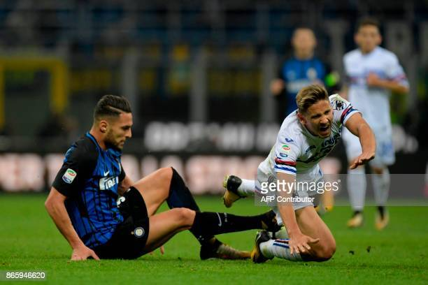Sampdoria's Belgian midfielder Dennis Praet is tackled by Inter Milan's Italian defender Danilo D'Ambrosio during the Italian Serie A football match...