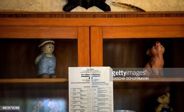 A sample of a voting paper is fixed on a cupboard with knickknacks at a polling station in Breckerfeld near Wuppertal western Germany during regional...