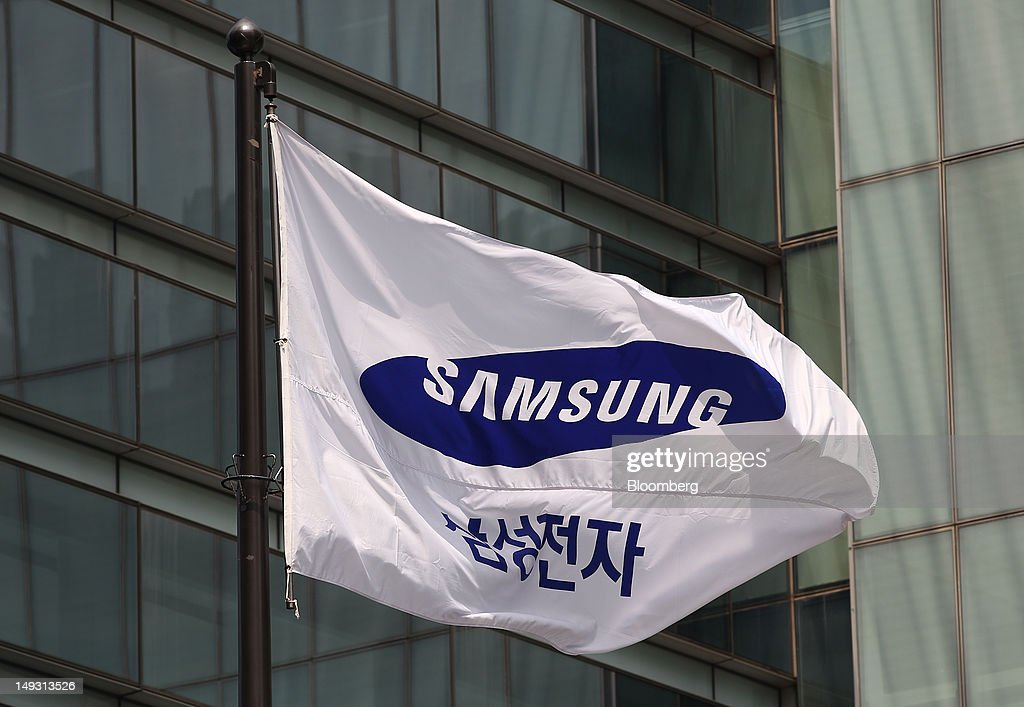A Samsung Electronics Co. corporate flag flies outside the company's Seocho offices in Seoul, South Korea, on Thursday, July 26, 2012. Samsung, the world's largest maker of TVs and mobile phones, reported second-quarter profit that missed analysts' estimates after chip prices weakened and smartphone output failed to keep up with demand. Photographer: SeongJoon Cho/Bloomberg via Getty Images