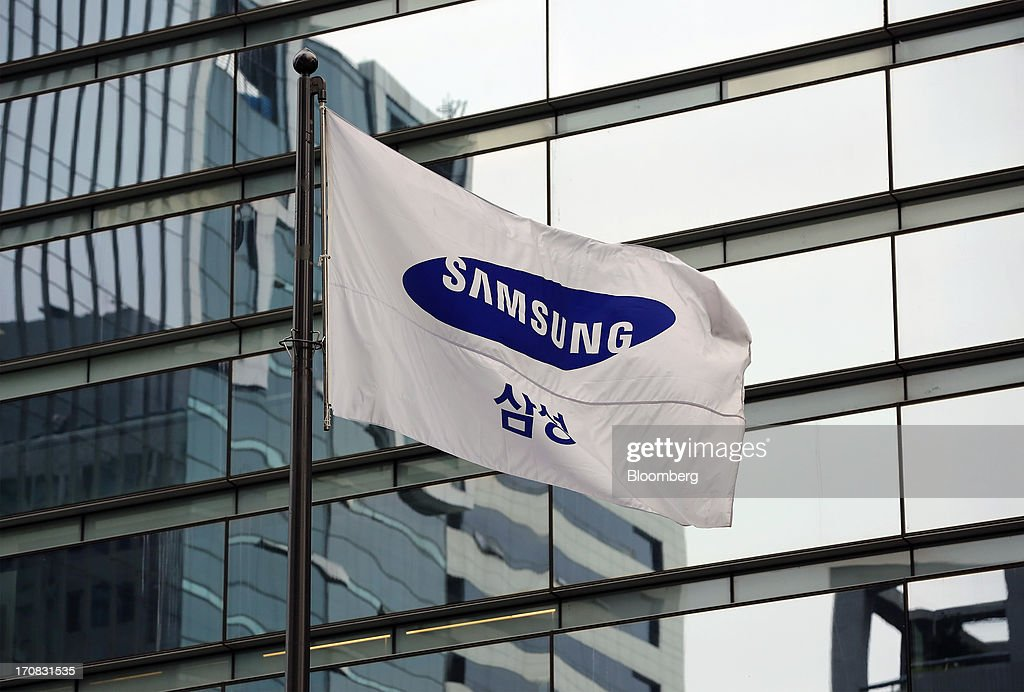 A Samsung Electronics Co. corporate flag flies outside the company's Seocho office building in Seoul, South Korea, on Tuesday, June 18, 2013. Facebook Inc. Chief Executive Officer Mark Zuckerberg, seeking to boost advertising sales from mobile devices, discussed potential partnerships with Samsung Electronics Co., according to the head of the South Korean companys handset division. Photographer: SeongJoon Cho/Bloomberg via Getty Images