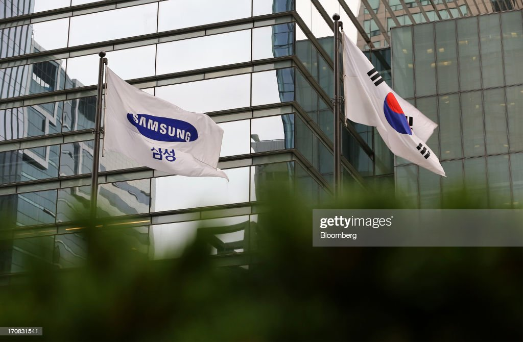A Samsung Electronics Co. corporate flag, left, and the South Korean national flag fly outside the company's Seocho office building in Seoul, South Korea, on Tuesday, June 18, 2013. Facebook Inc. Chief Executive Officer Mark Zuckerberg, seeking to boost advertising sales from mobile devices, discussed potential partnerships with Samsung Electronics Co., according to the head of the South Korean companys handset division. Photographer: SeongJoon Cho/Bloomberg via Getty Images