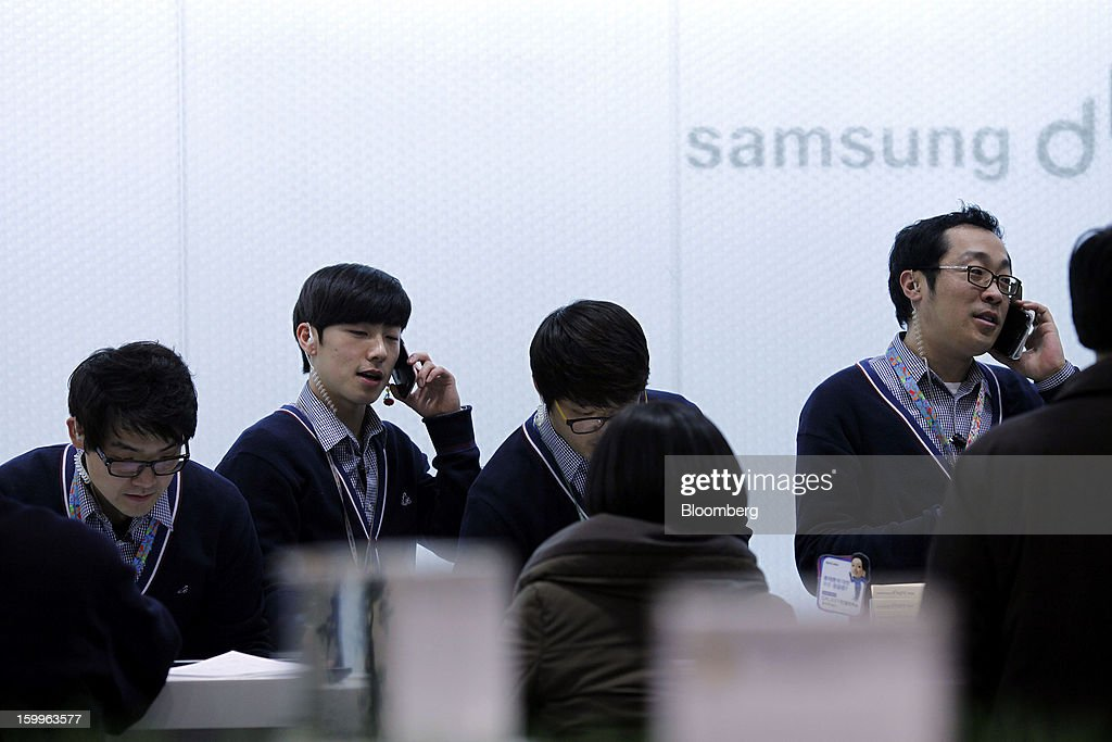 Samsung Electronics Co. employees talk on smartphones and serve customers at the Samsung d'light store in Seoul, South Korea, on Wednesday, Jan. 23, 2013. Samsung, in a preliminary statement of results on Jan. 8, reported an 89 percent jump in profit in the three months ended in December, boosted by its Galaxy line of smartphones. Photographer: Woohae Cho/Bloomberg via Getty Images