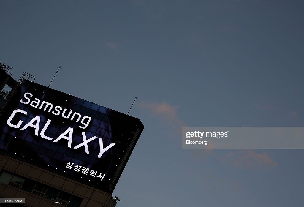 A Samsung Electronics Co. Galaxy advertisement stands illuminated at dusk in Gwanghwamun Square in Seoul, South Korea, on Tuesday, Oct. 22, 2013. Samsung Electronics is scheduled to release third-quarter earnings on Oct. 25. Photographer: SeongJoon Cho/Bloomberg via Getty Images
